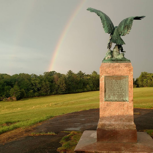 a back view of Utica's Eagle monument looking out at a rainbow in the background